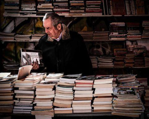 mężczyzna przegląda książkę na stoisku księgarskim