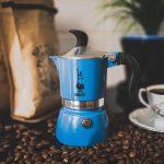 kawiarka moka stojąca na stole pośród ziaren kawy