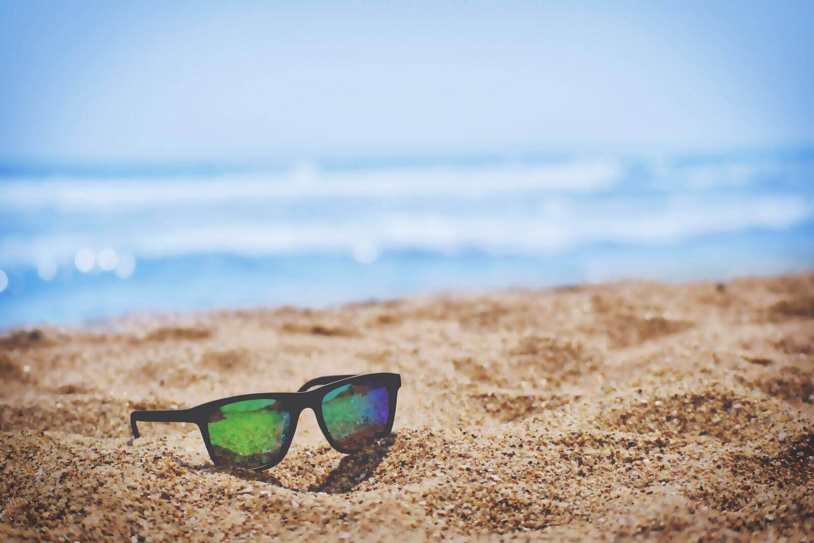 okulary przeciwsłoneczne leżące na plaży